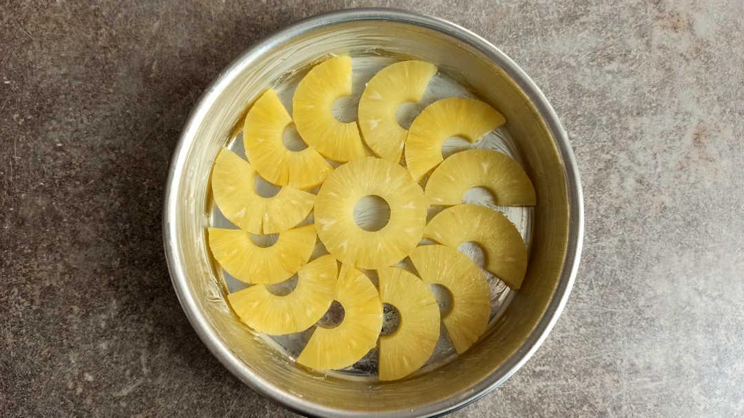 Pour un joli gâteau ananas caramel, disposer les rondelles d'ananas dans le fond du moule beurré