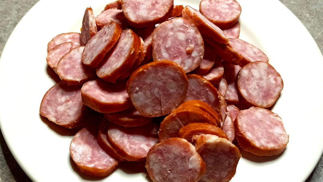 Couper les saucisses de Montbéliard en fines rondelles