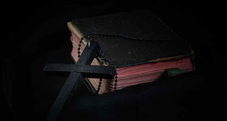 black cross leaning on black hardcover bible