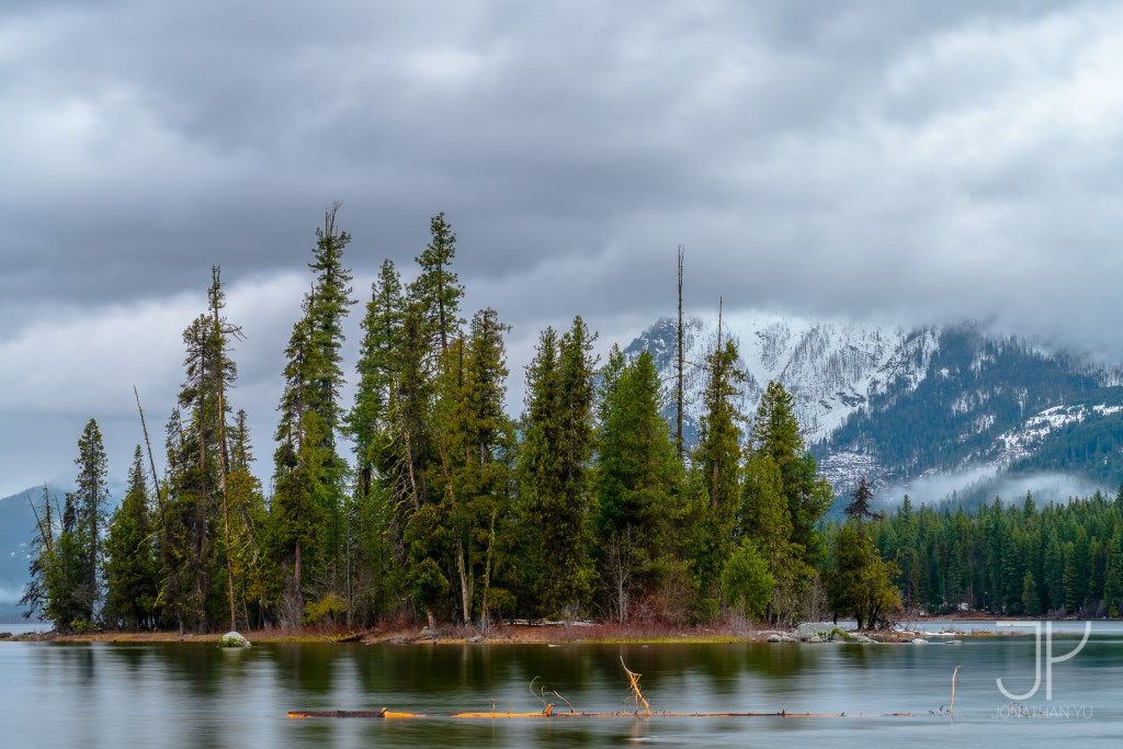 An island of peace surrounded by stormy clouds and snowy peaks