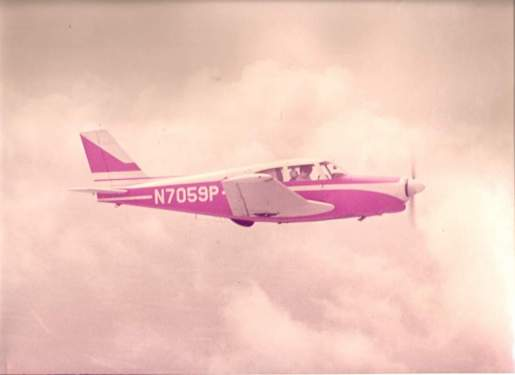 Dad flying Piper Comanche, circa 1970. Mom is his co-pilot.