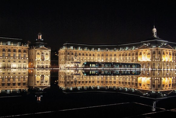 A nighttime shot of a French chateaux, perfectly reflected on water