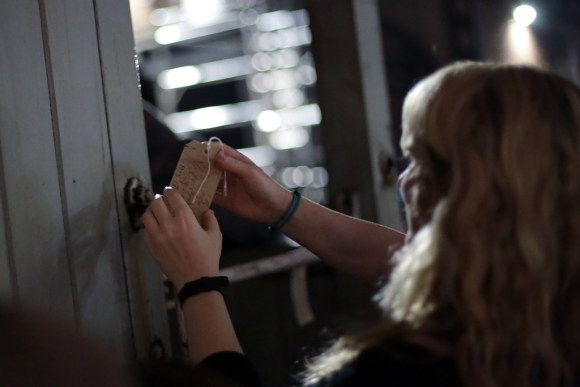 A woman ties a luggage tag containing her memories to a door in the Museum of Science and Industry, Manchester. From the immersive show Inside The Memory Palace