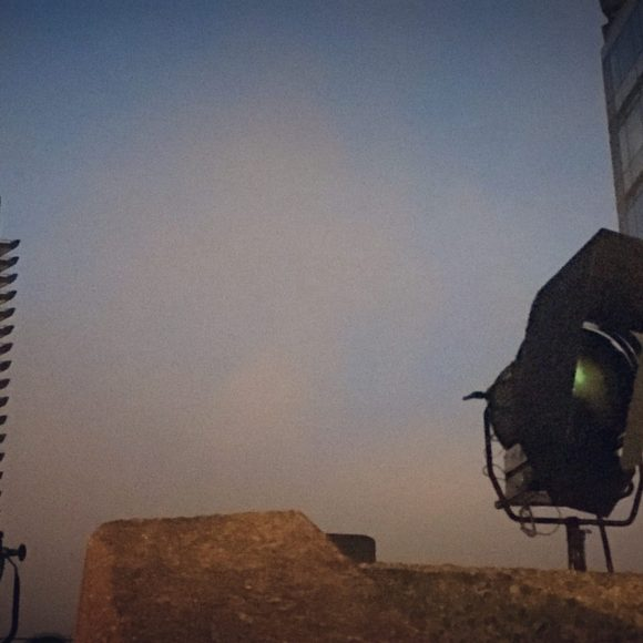 An Arri 12K light sits high up on the Barbican Estate with the sunset in the background