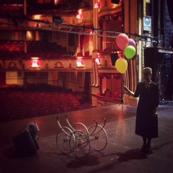 A woman stands on an empty stage, holding a bunch of balloons. We see a grand, empty auditorium behind her.