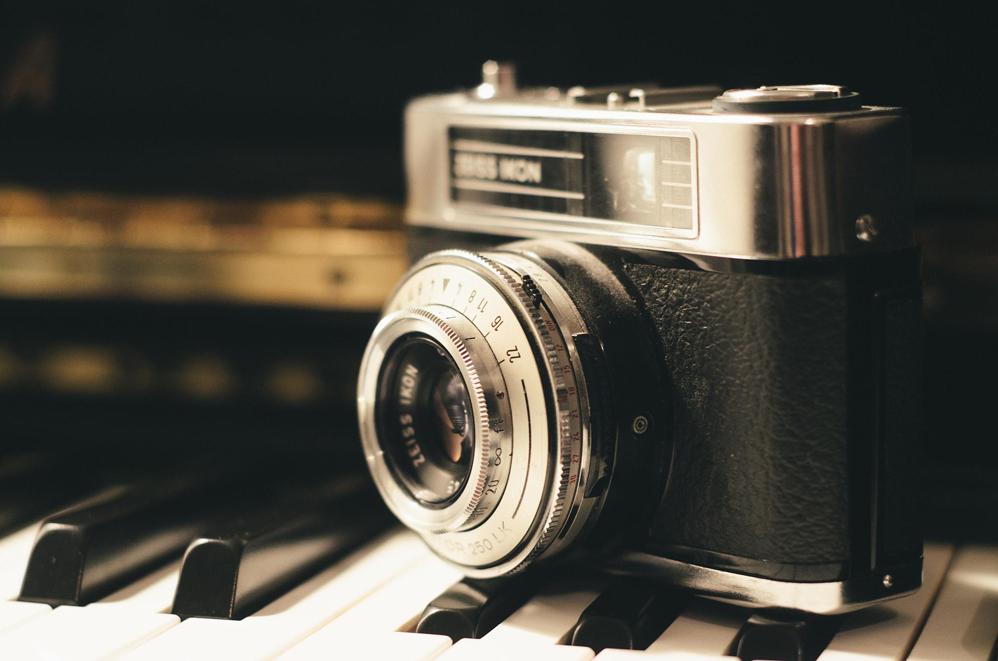 vintage film camera sits atop piano keys