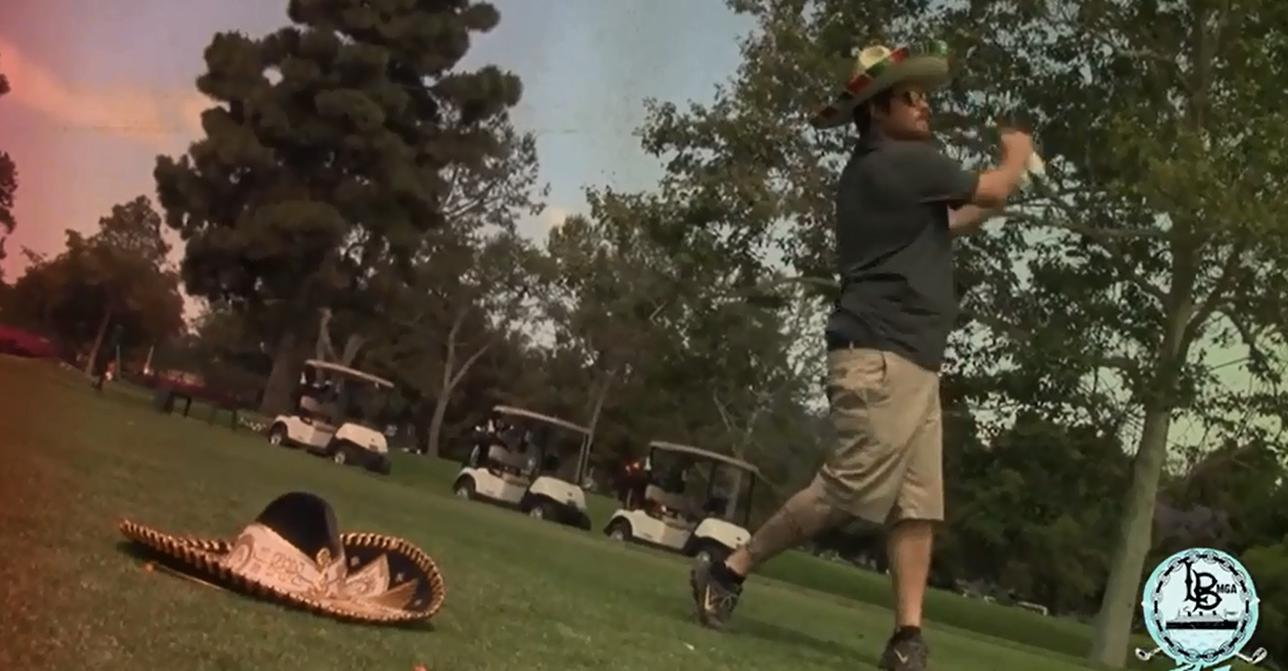 Golfer swinging club wearing a sombrero
