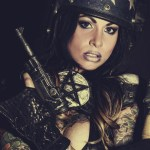Portrait of brunette model in leather armor with gun.