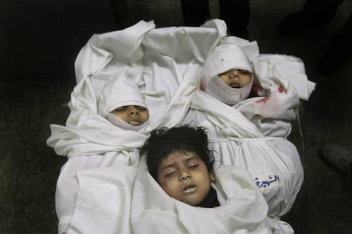 En el depósito de cadáveres de Beit Lahia, tres niños palestinos, de cinco que fueron abatidos por un misil israeli, todos de la misma familia. (Foto AP)