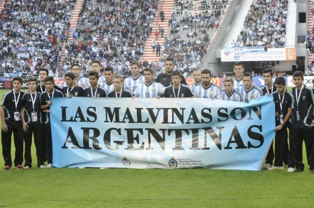 Jogadores argentinos posam para foto com banner reiterando posse das Ilhas Malvinas pelo país