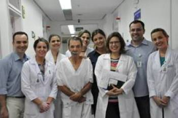 Paciente Danúbio, ladeado pela equipe multidisciplinar do Proface, formada por profissionais da Fonoaudiologia, Fisioterapia, Nutrição, Psicologia, Assistência Social, Enfermagem e médicos