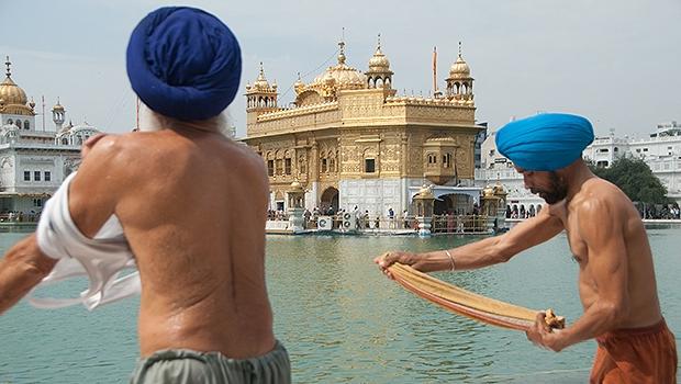 Homens torcem roupas após banho no lago do Templo de Ouro, em Amritsar