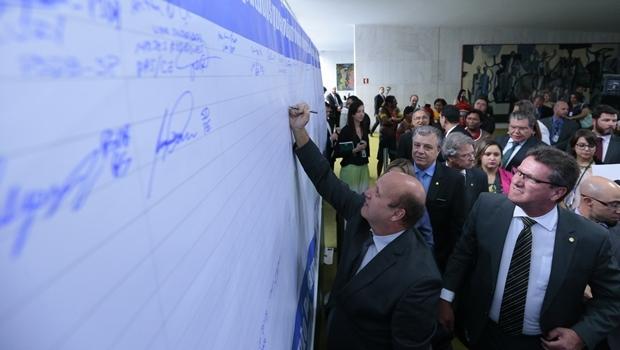 Célio Silveira assinando o painel | Foto: Alexssandro Loyola