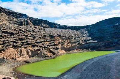El Charco Verde (the Green Lagoon) is a former volcanic crater infiltrated by sea water denser and saltier than that of the Dead Sea. Its unusual green color is caused by the algae that has taken over the lake.