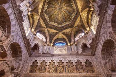 Above the mihrab, a dazzling dome is lavishly covered with gold mosaic in a radial pattern.