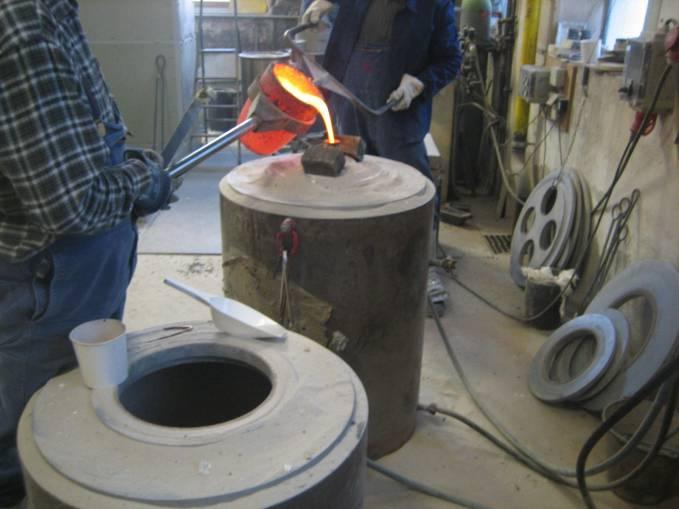 Molten bronze being cast into investment mold under vacuum