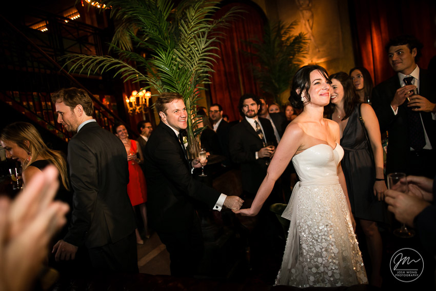 The bride and groom enter the Jane Hotel Ballroom to a family and friends cheering. The Jane Hotel wedding pictures by Josh Wong Photography