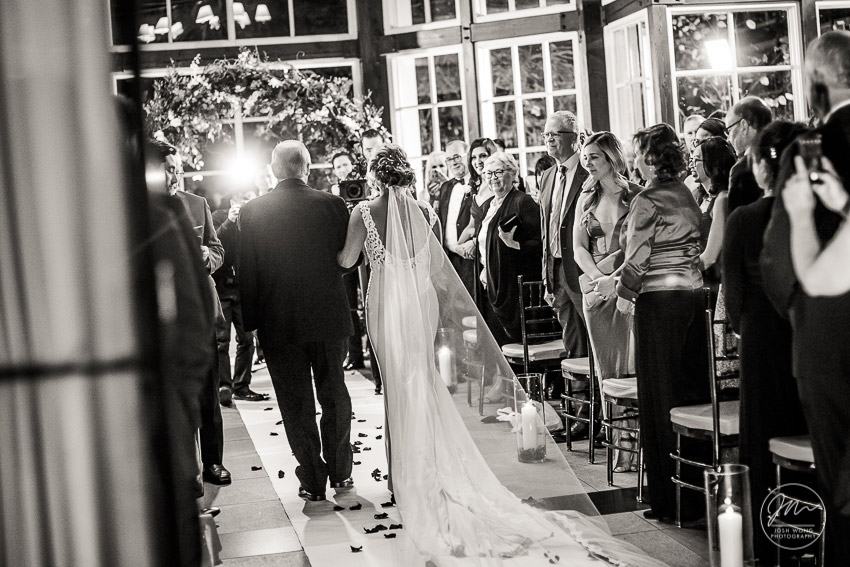 The Father of the bride escorts the bride down the aisle. Wedding photography by NYC wedding photographer Josh Wong. Central Park Boathouse.