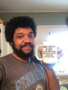 "Jotham Austin, II holding mug that says, ""Being a writer is easy. It's like riding a bike. Except the bike is on fire. You're on fire. Everything is on Fire."""