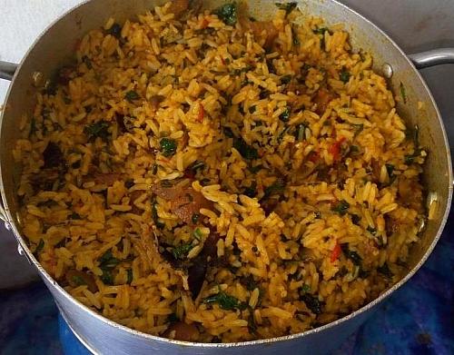 Adding of basil (scent leaves in plam oil jollof rice (native rice)