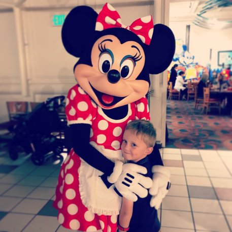 Minnie Mouse hugging Andrew at Chef Mickey's