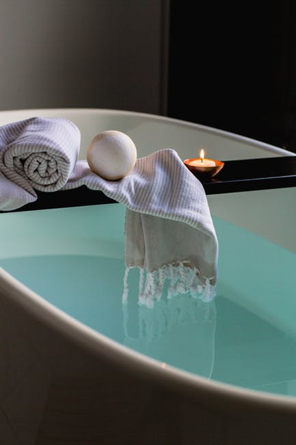 A warm bath with a candle and washcloths.