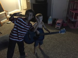 "Malachi and one of our ""adopted brothers"" during family devotions (and No, Malachi is not a prodigy at guitar...he just THINKS he is)"