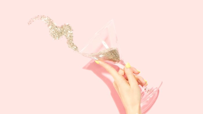 a woman holding a martini glass and some glitter