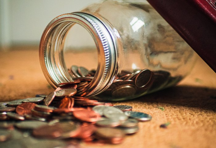 A jar of money, with coins spilling out, to show that personal essays do not pay well