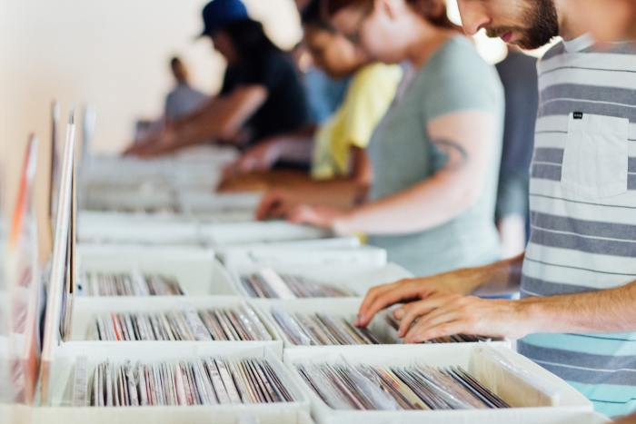 people looking through records in a box