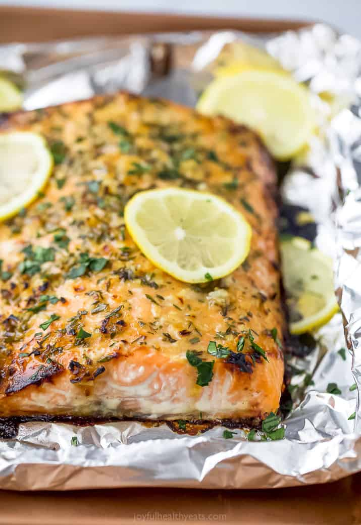close up photo of baked honey garlic salmon in foil topped with lemon