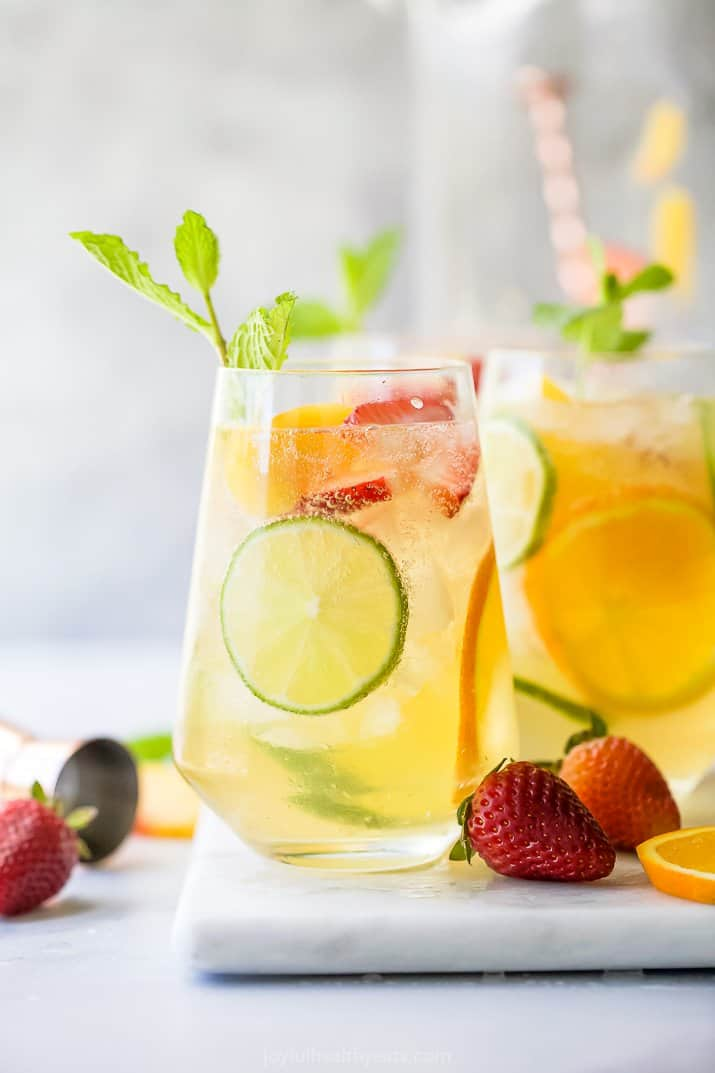 strawberry peach moscato sangria in a glass garnished with citrus