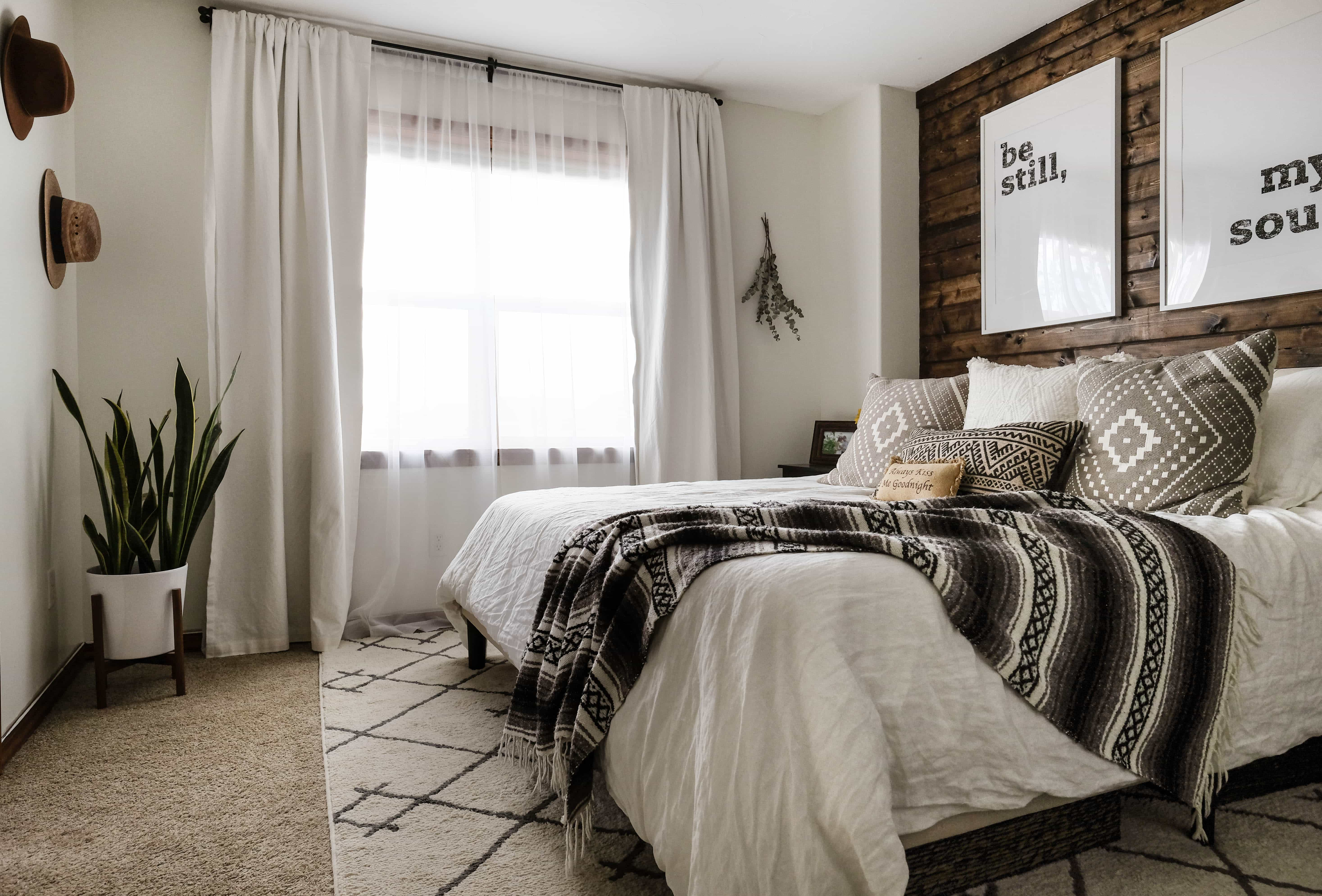 A Decorated bedroom with a walnut stained DIY wood plank accent wall