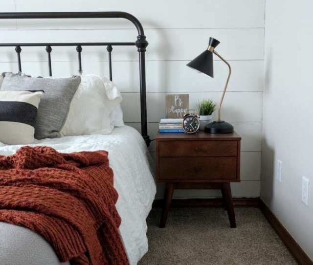 A Nightstand Styled With Books Alarm Clock And A Lamp In A Farmhouse Bedroom