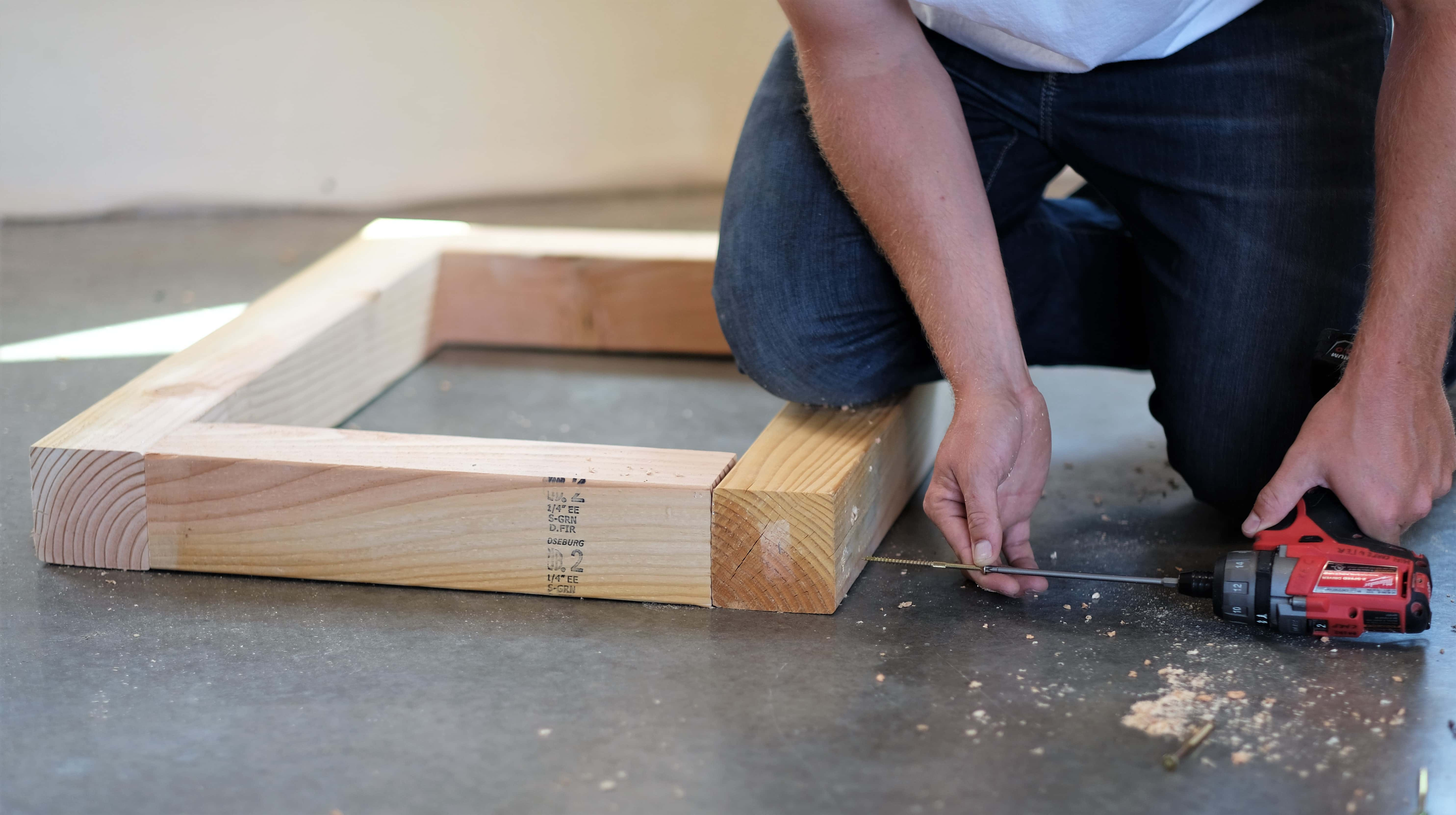 man using a drill to screw boards together for a rustic coffee table