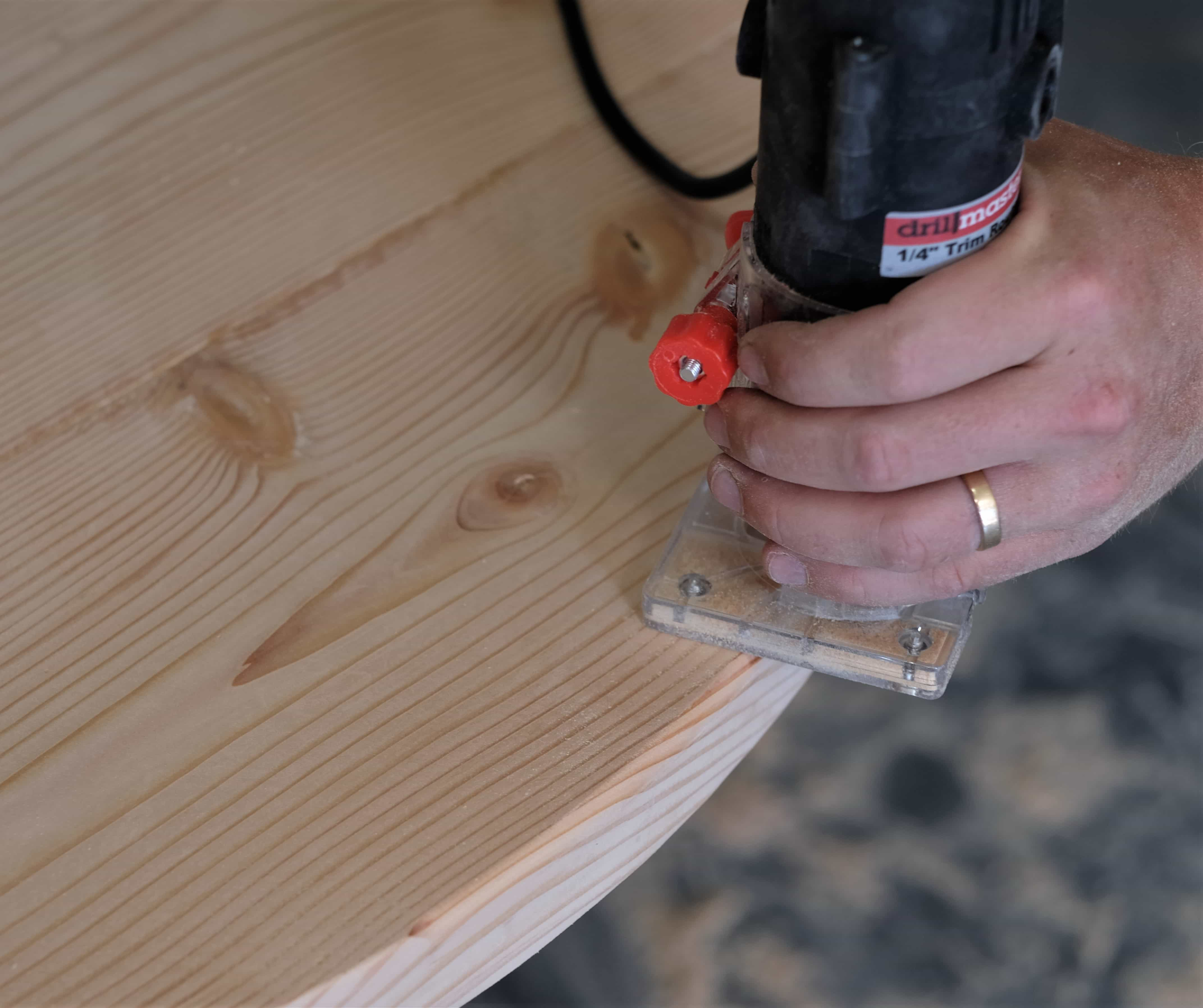 Man using router to round the edges of a rustic coffee table