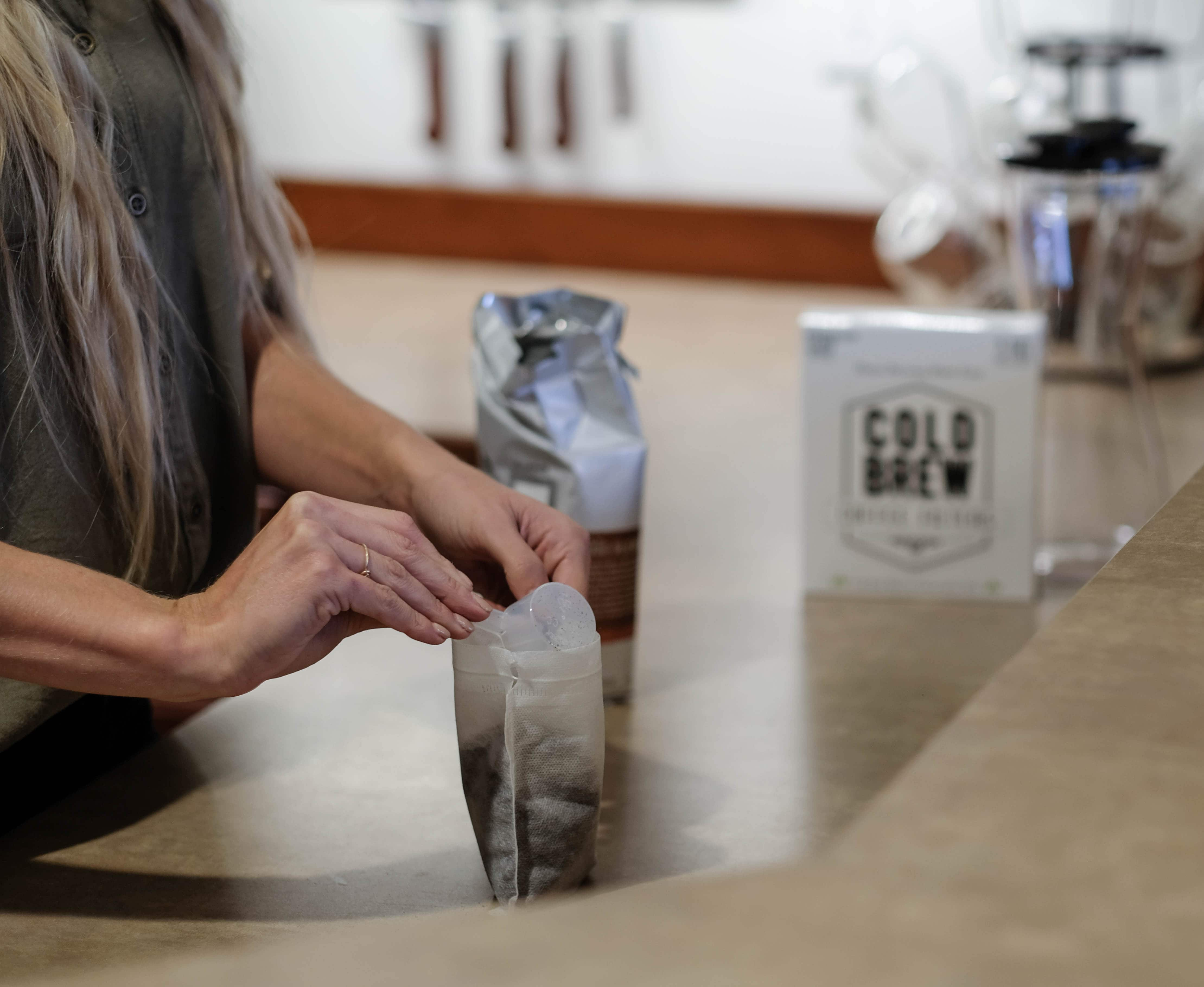 pouring coffee grinds into cold brew coffee filter bag
