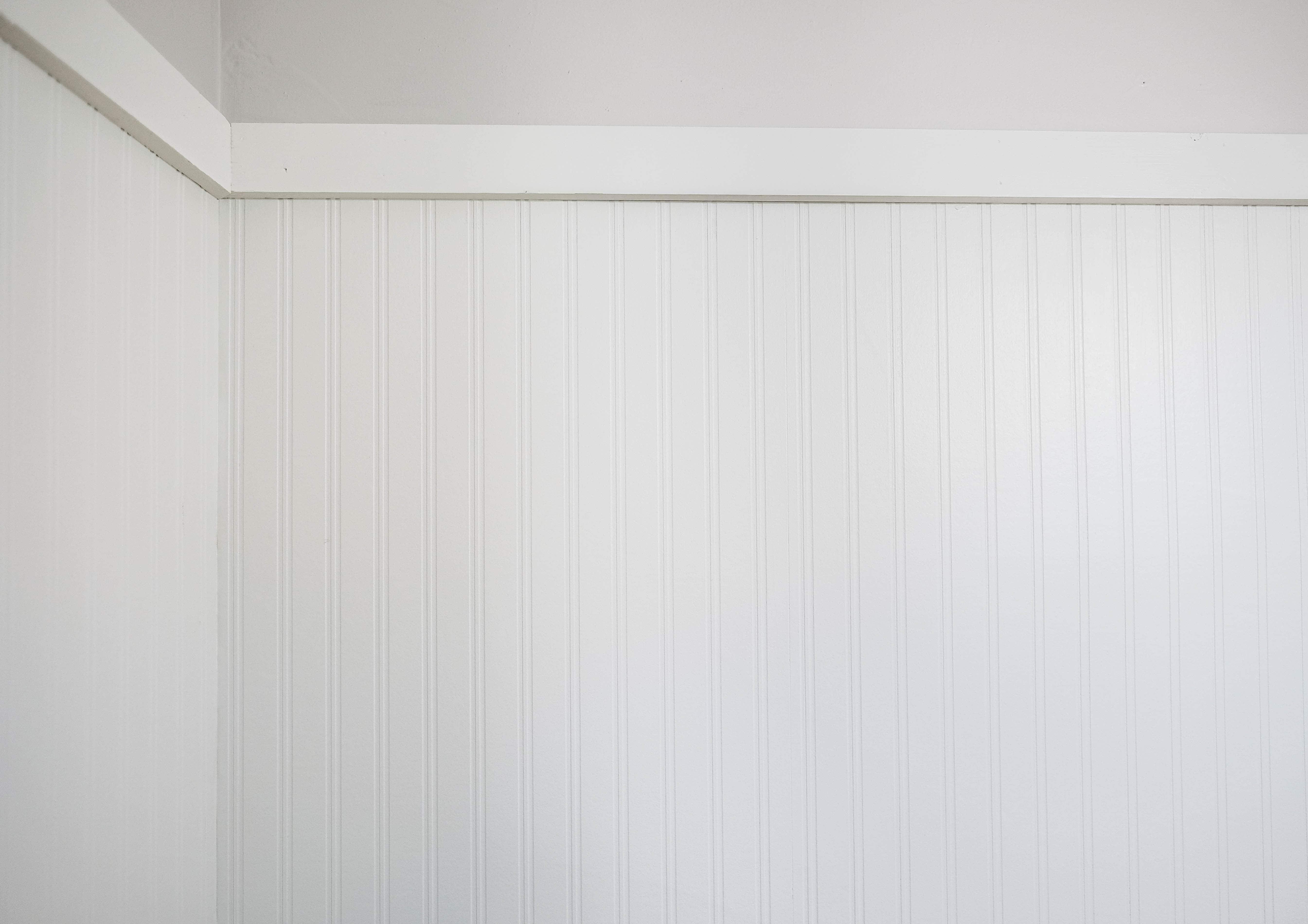 White beadboard wallpaper against light grey wall