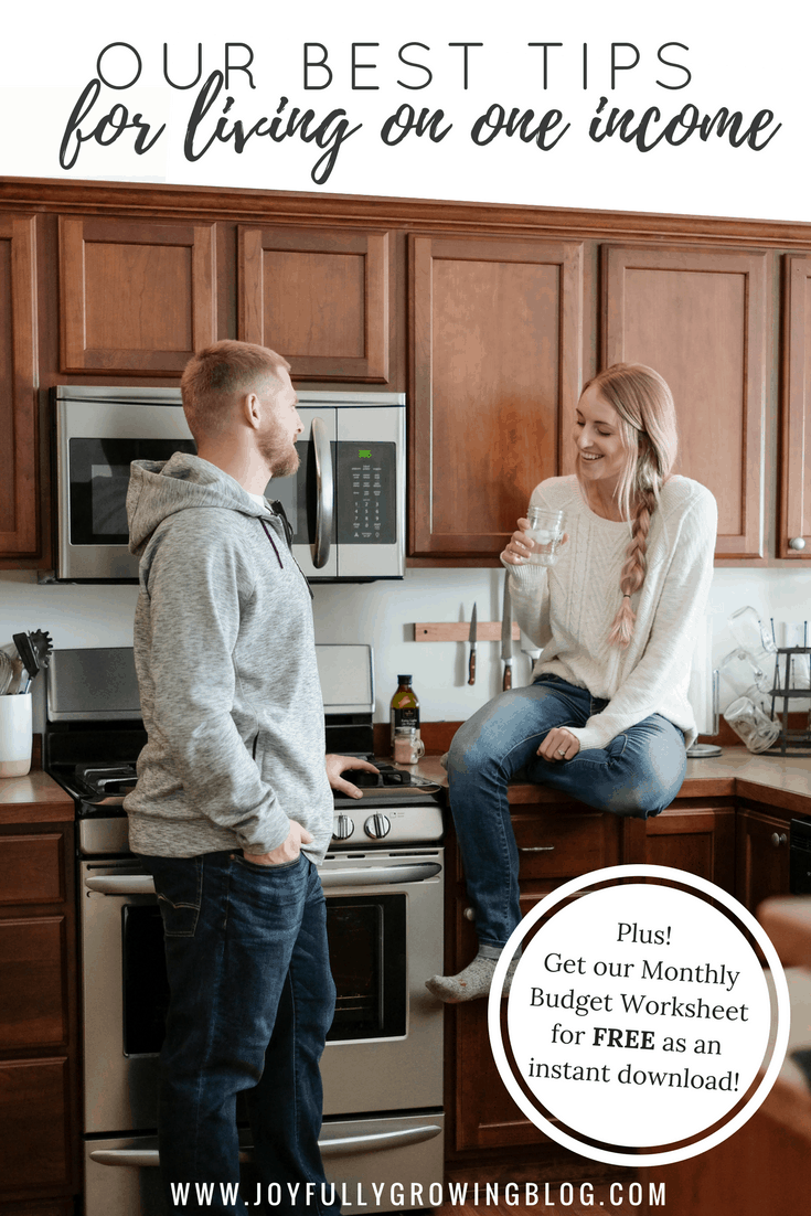 """Two people in the kitchen, one sitting on the counter talking about their budget. Text overlay reads """"Our Best Tips for living on one income"""""""
