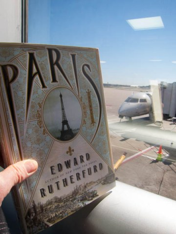 Holding the book Paris by Edward Rutherfurd in front of the plane at Lambert Airport