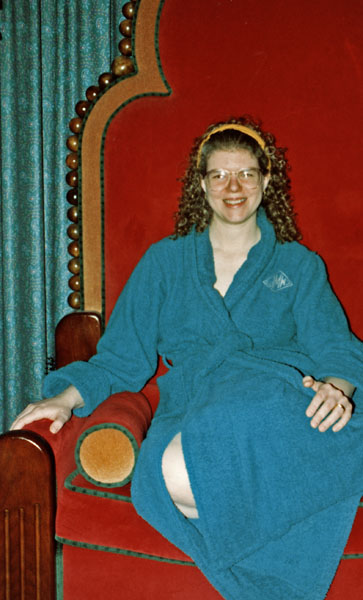Woman in bathrobe sitting on a large red chair