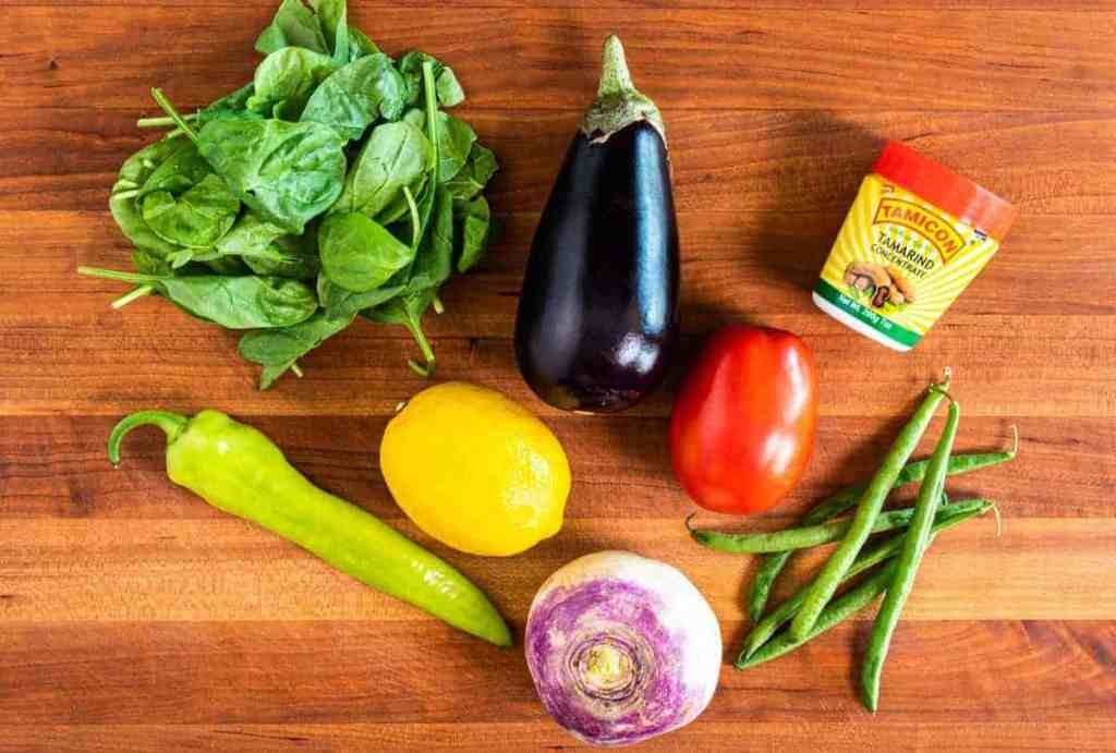 Sinigang Pork ingredients on cutting board spinach, eggplant, lemon, tomato, Anaheim pepper, green beans, rutabaga and tamarind concentrate