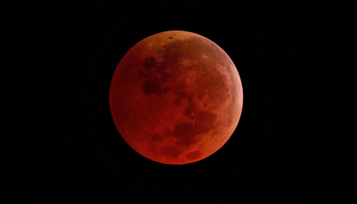 As the Moon moves completely into the umbra, it turns a reddish-orange color.