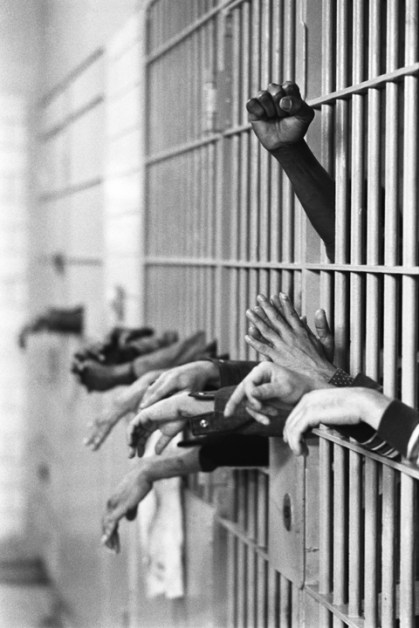 Manhattan, New York City, NY. September 28th, 1972. Hands from behing the bars at Toms Prison. Standing on Center Street at Leonard Street, and was built in 1840 with granite from the old Bridewell Prison in City Hall.