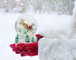 A person carrying a snow-globe through the snow.