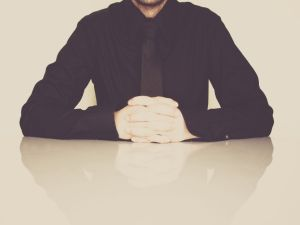 A businessman in a black shirt and tie sitting behind a white table.