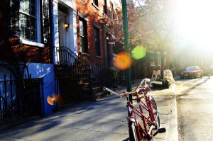 Brownstones and a bike in front of them.