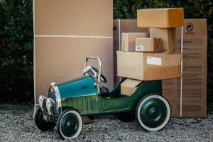 Moving boxes in various sizes and a small green car.