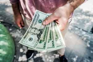 Man holding several 20 dollar bills.