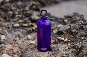 How to pack liquids for moving like this purple gym bottle places on rocks by the river